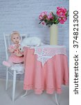 Small photo of little 8 months girl in a rose knitting dress sitting on a chair with white rabbit like Alice in wonderland, mad tea party