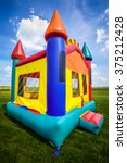 Small photo of Bounce house inflatable jumpy castle in a large open yard.