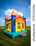Small photo of Children's bouncy house castle in a large open yard.