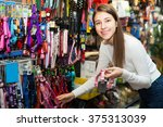 Stock photo happy girl selecting collars and leads in petshop 375313039