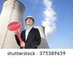 Engineer in front of cooling towers with stop sign