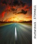 Asphalt road to city under dramatic sunset