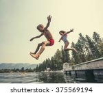 kids jumping off the dock into... | Shutterstock . vector #375569194