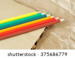 six colored pencils on brown... | Shutterstock . vector #375686779