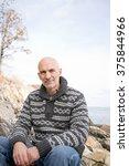 mature man sitting on rocks | Shutterstock . vector #375844966