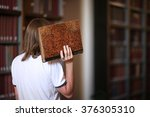 Small photo of Academic session; rear view of a man with an old book in hand