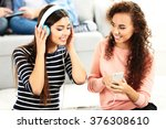 two teenager girls listening to ... | Shutterstock . vector #376308610