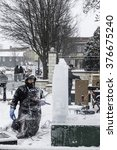 Small photo of DOWNERS GROVE, ILLINOIS/USA - FEBRUARY 14, 2016: A kneeling sculptor in winter garb pauses to contemplate his work during a demonstration of ice carving at a civic festival on a snowy Valentine's Day.