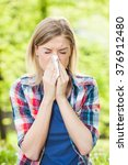 Small photo of Woman with with allergy symptom blowing nose