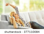 young woman on a sofa listening ... | Shutterstock . vector #377110084