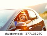 smiling woman driving a car at... | Shutterstock . vector #377138290