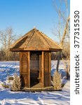 Small photo of Wooden alcove in winter surrounded by snow and blue sky