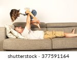 dad lying on sofa and lifting... | Shutterstock . vector #377591164