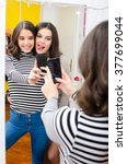 Two Teenage Girls Taking Selfi...