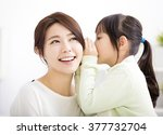 mother and daughter whispering... | Shutterstock . vector #377732704