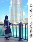 Small photo of arabic woman looking to burj khalifa, arabic fashion style, abaya style