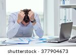 Small photo of business, people, paperwork and deadline concept - stressed businessman with papers and charts sitting at table in office