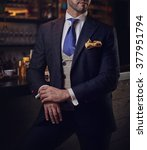 suited man posing in a bar   Shutterstock . vector #377951794