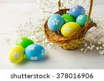 Hand-painted decorated Easter eggs in the basket with small white baby's breath flowers on a white wooden background, close up. Easter eggs. Easter background