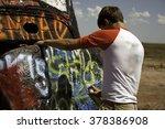 A Teenage Boy Spray Painting A...