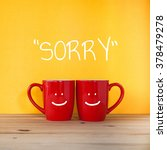 Small photo of Sorry word. Two cups of coffee and stand together to be heart shape on yellow background with smile face on cup.