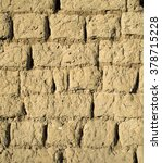 Small photo of Wall of old adobe house closeup in sunny day