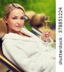 Small photo of people, beauty, lifestyle, holidays and relaxation concept - beautiful young woman in white bath robe lying on chaise-longue and drinking champagne at spa