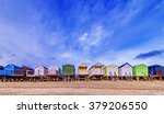 beach huts with a bright blue...