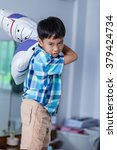 Small photo of An aggressive asian child. Boy looking furious. Kid will throw pillow inside bedroom. Negative human face expressions, emotions .problem families concept.