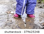 little girl jumps into a puddle | Shutterstock . vector #379625248