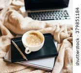 Small photo of A cup of coffee, diary and address book with the laptop on the bed with a beige plaid