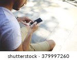 Cropped image of young man chatting on mobile phone with blank copy space screen for your advertising text message or content, bearded male viewing photos on cell telephone during free time outdoors
