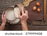 Small photo of baker sift the flour to make bread on a wooden dark surface, top view