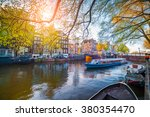 Stock photo spring scene in amsterdam city tours by boat on the famous dutch canals colorful evening 380354470