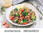Stock photo  quinoa salad with broccoli sweet potatoes and tomatoes on a rustic wooden table superfoods concept 380364823