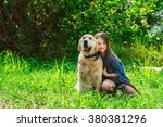 Stock photo little girl playing with her big dog outdoors in rural areas in summer kid with golden retriever 380381296
