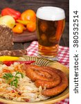 Small photo of Sausages and sauerkraut with glass of beer, vertical