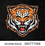 aggressive tiger face. on dark... | Shutterstock .eps vector #380777488