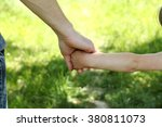 the parent holds the hand of a... | Shutterstock . vector #380811073