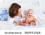 mother and child on a white bed.... | Shutterstock . vector #380951968