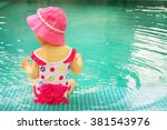 baby sitting near swimming pool. | Shutterstock . vector #381543976