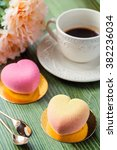 Small photo of Heart shaped mini mousse cakes covered with chocolate velour with cup of coffee and flowers on green table in cafe. Modern european cake