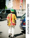 Small photo of Rastaman wearing tradition al rasta hat, white pants and colorful traditional motive shirt walking on the streets of a modern city