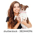 Stock photo portrait of a pretty young brunette woman holding a little mixed breed dog both are looking into 382444396
