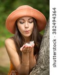 Small photo of cute girl in orange hat blows a feather palm