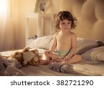 Stock photo sweet little girl eighteen months with diaper in bed sunset light cats toys 382721290
