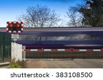 Small photo of Motion blurred train speeding through a level crossing