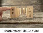 Small photo of Dominos standing in U shape with the ending ones holding the words Start and Finish and a finger about to knock down the first one.