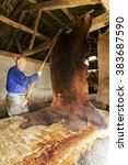 Small photo of traditional tanner carring the leather to the drying room in the antique adobe tannery