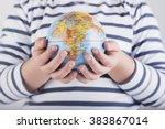 child's hand with globe